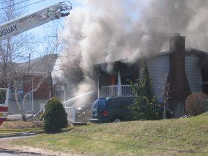 Maison victime d'un feu entourée de fumée