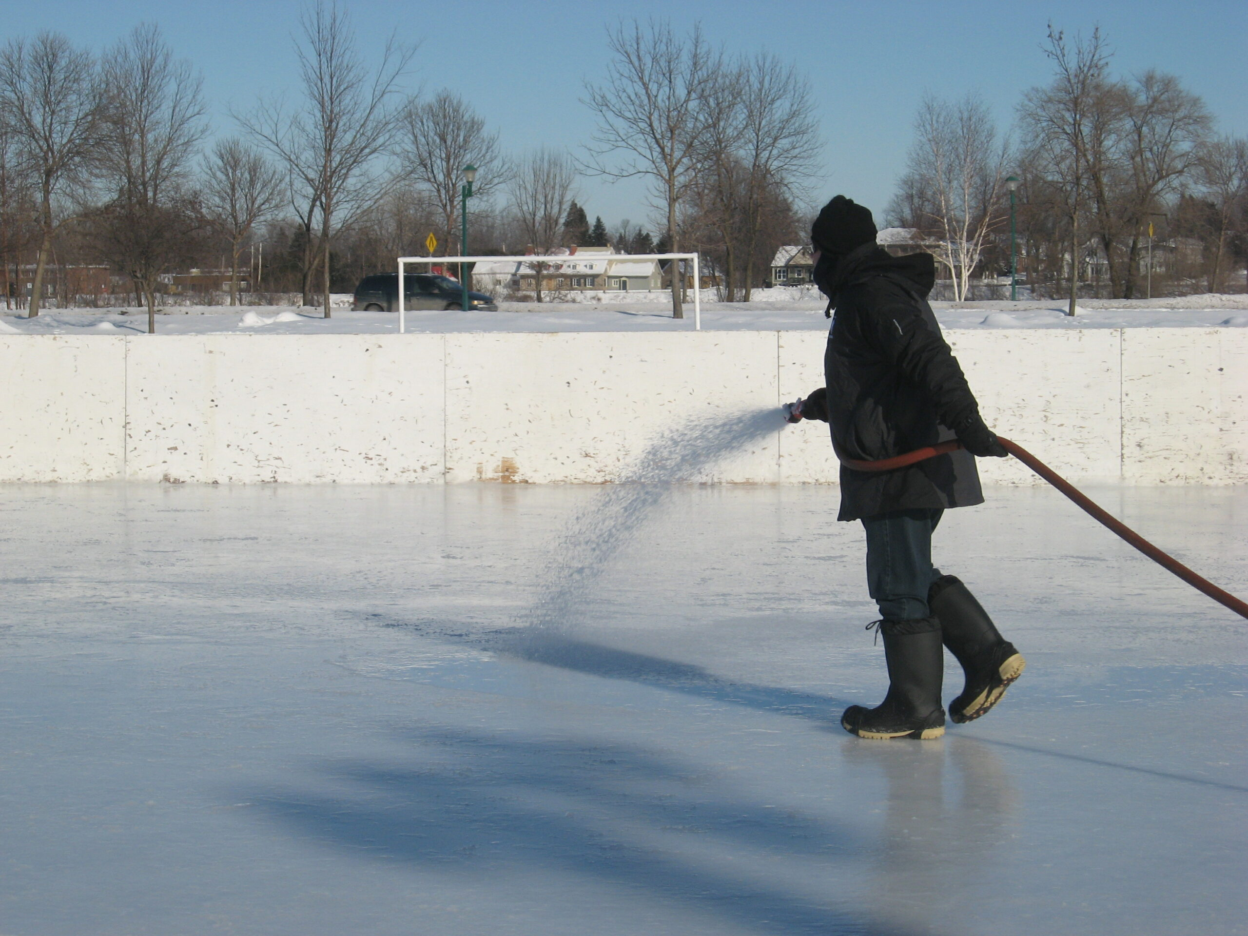 worker spaying water on ice rink