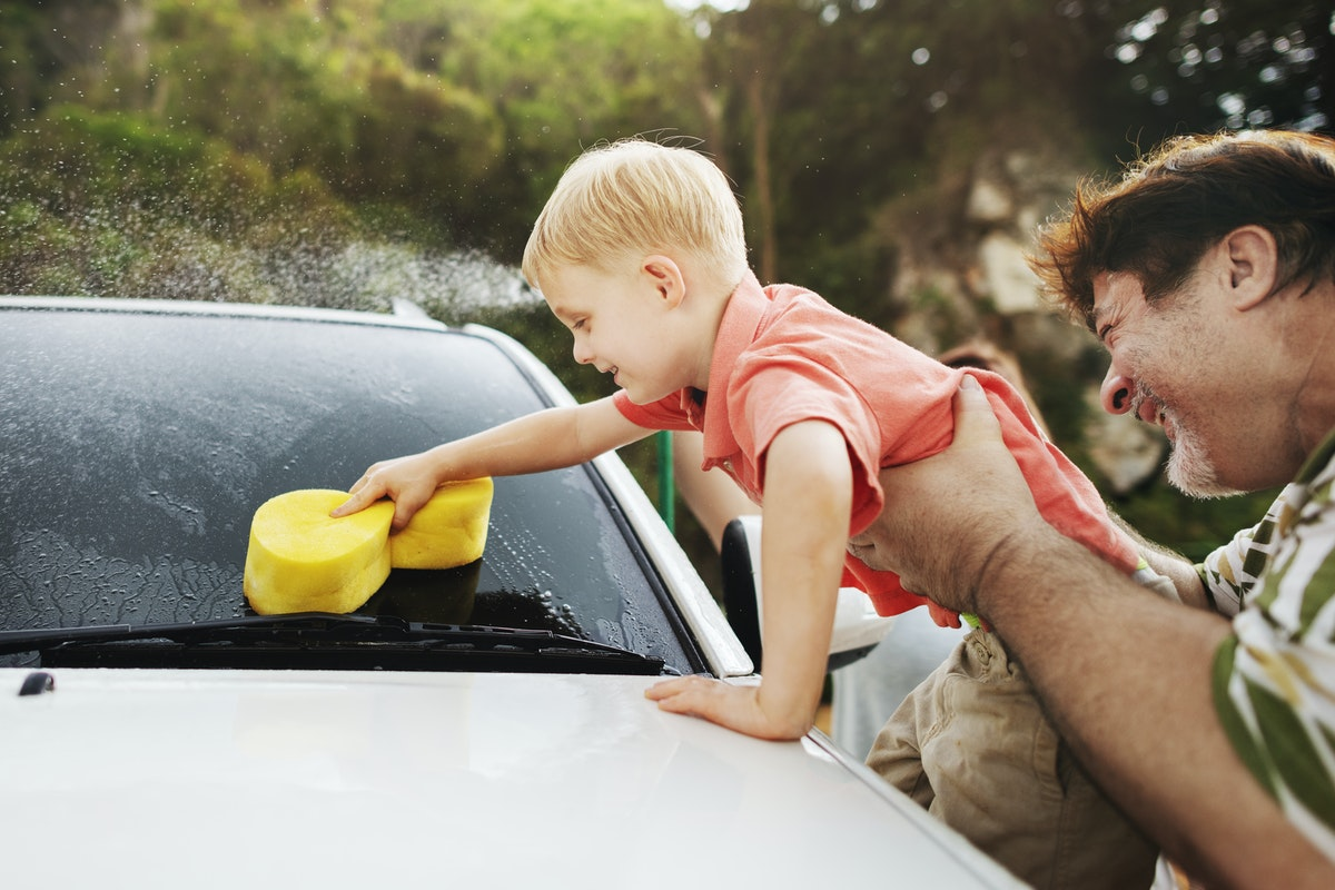 child washing a car with his father