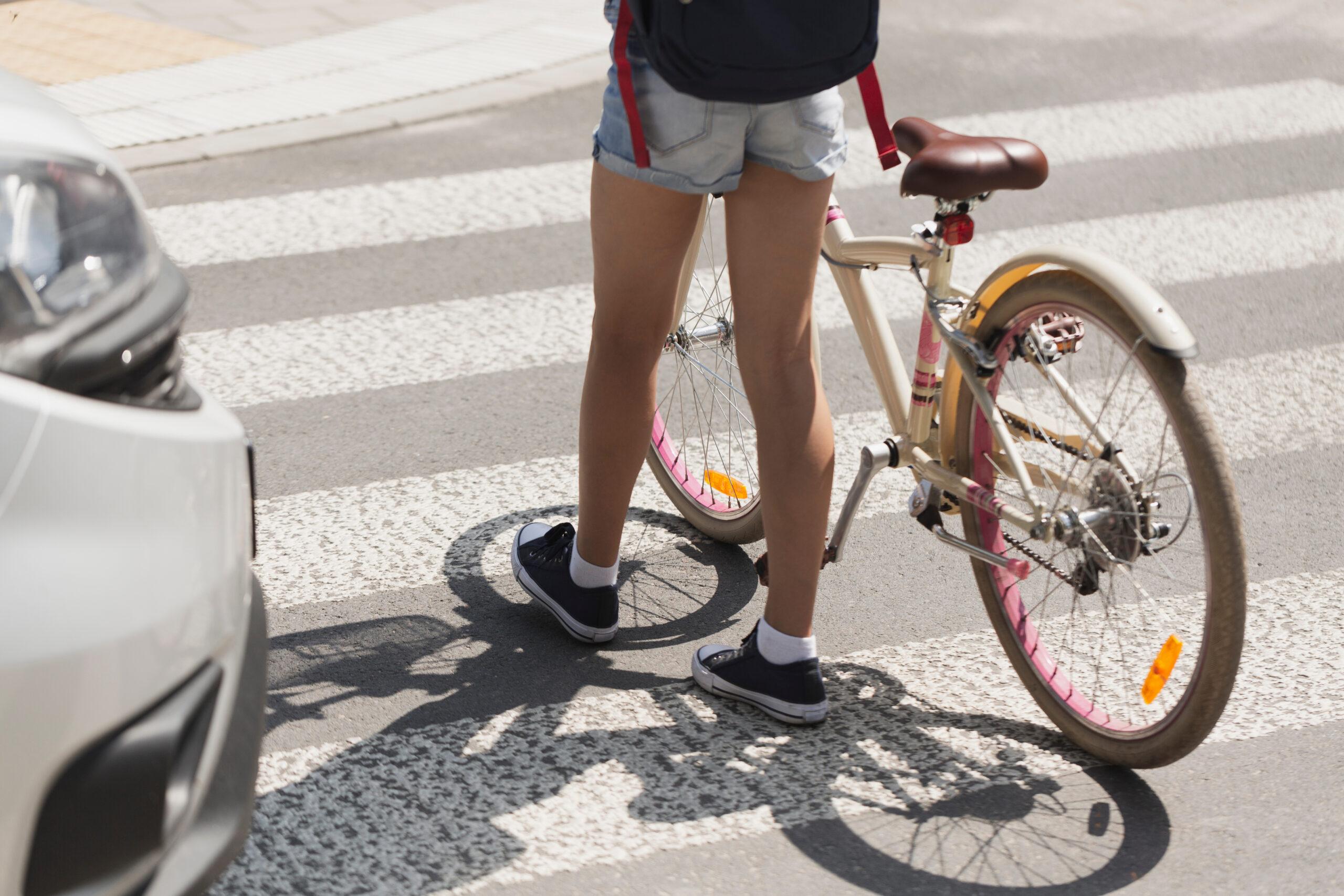 Personne qui traverse une rue avec son vélo